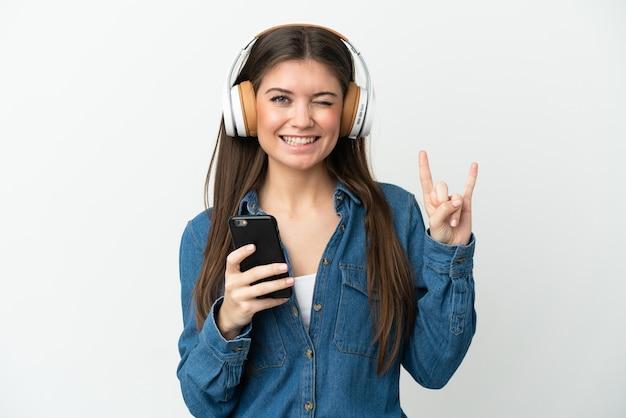 Giovane donna caucasica isolata su sfondo bianco ascoltando musica con un cellulare che fa gesto rock