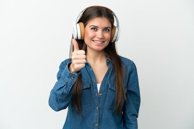 Giovane donna caucasica isolata su sfondo bianco ascoltando musica e con il pollice in alto