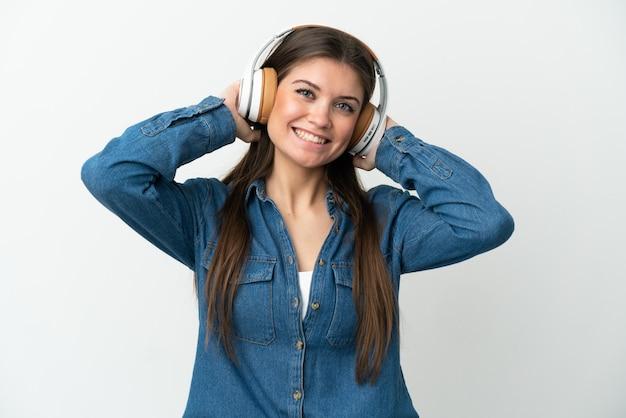 Giovane donna caucasica isolata su sfondo bianco ascoltando musica