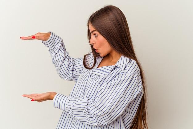 Giovane donna caucasica isolata su sfondo bianco che mostra il numero uno con il dito.