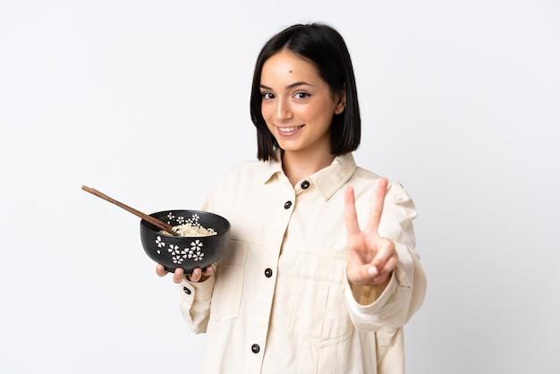 Giovane donna caucasica isolata su fondo bianco che sorride e che mostra il segno di vittoria