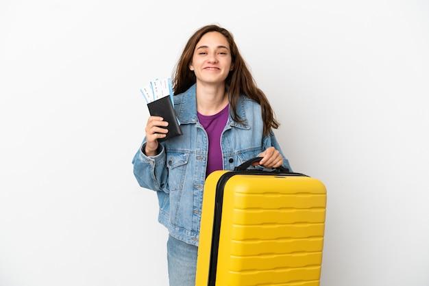 Giovane donna caucasica isolata su sfondo bianco in vacanza con valigia e passaporto