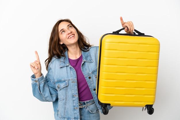 Giovane donna caucasica isolata su sfondo bianco in vacanza con valigia da viaggio e rivolta verso l'alto