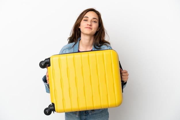 Giovane donna caucasica isolata su sfondo bianco in vacanza con valigia da viaggio