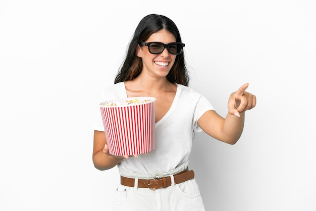 Giovane donna caucasica isolata su sfondo bianco con occhiali 3d e con in mano un grosso secchio di popcorn mentre punta davanti