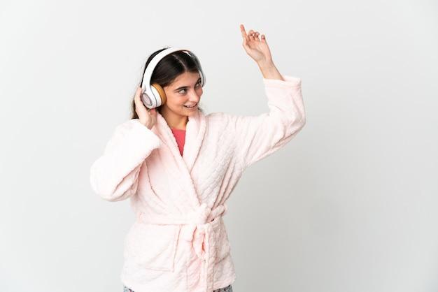 Giovane donna caucasica isolata su bianco in pigiama e tenendo un cuscino e ascoltando musica