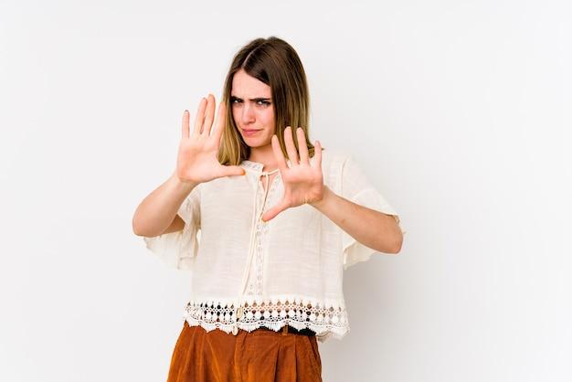 Giovane donna caucasica isolata over white che rifiuta qualcuno che mostra un gesto di disgusto.