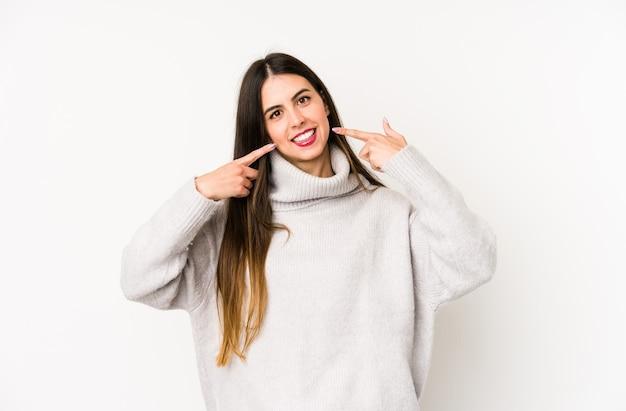 La giovane donna caucasica isolata sui sorrisi bianchi, puntando le dita alla bocca.