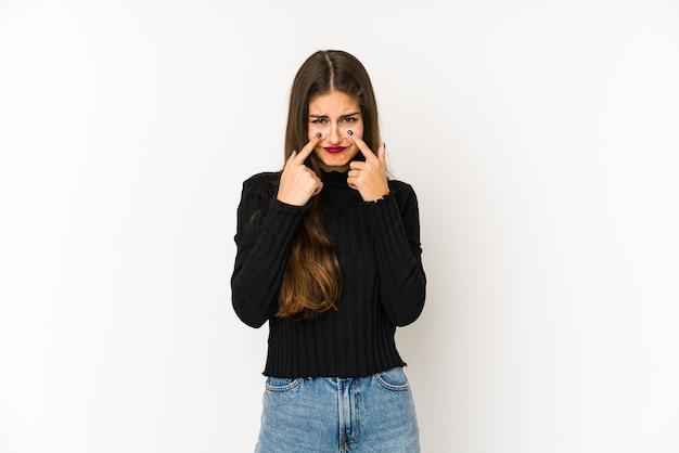 Giovane donna caucasica isolata sul muro bianco piangendo, insoddisfatta di qualcosa, agonia e concetto di confusione.