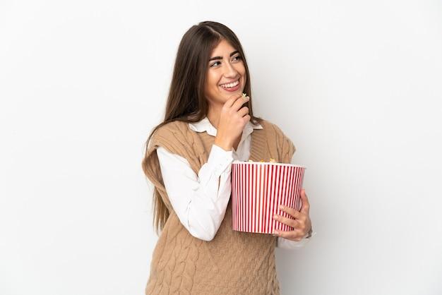 Giovane donna caucasica isolata sulla parete bianca che tiene un grande secchio di popcorn