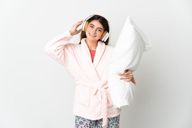 Giovane donna caucasica isolata sul muro bianco in pigiama e tenendo un cuscino e ascoltando musica