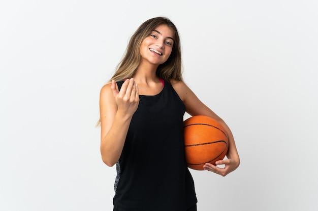 Giovane donna caucasica isolata sul muro bianco, giocare a basket e fare il gesto in arrivo
