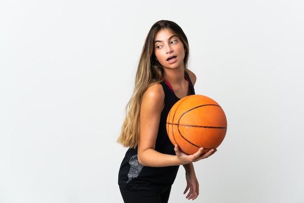 Giovane donna caucasica isolata sul muro bianco, giocando a basket