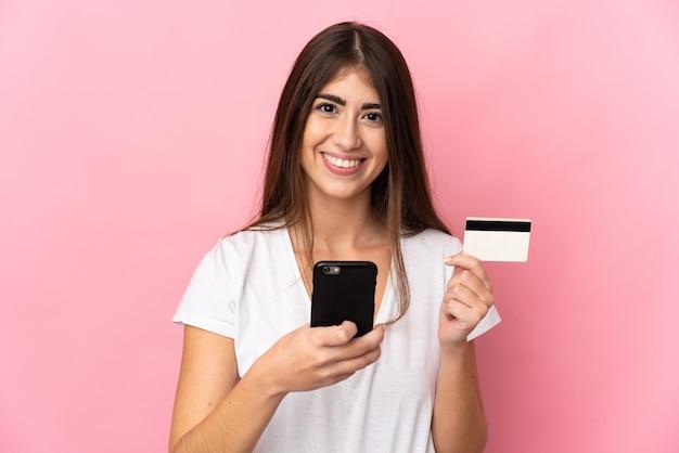 Giovane donna caucasica isolata con il cellulare con carta di credito