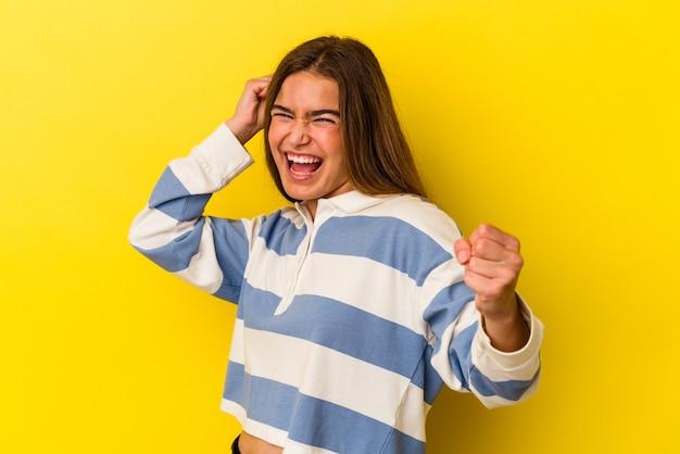 Giovane donna caucasica isolata su sfondo giallo ballare e divertirsi.