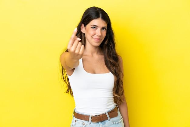 Giovane donna caucasica isolata su sfondo giallo che fa un gesto imminente