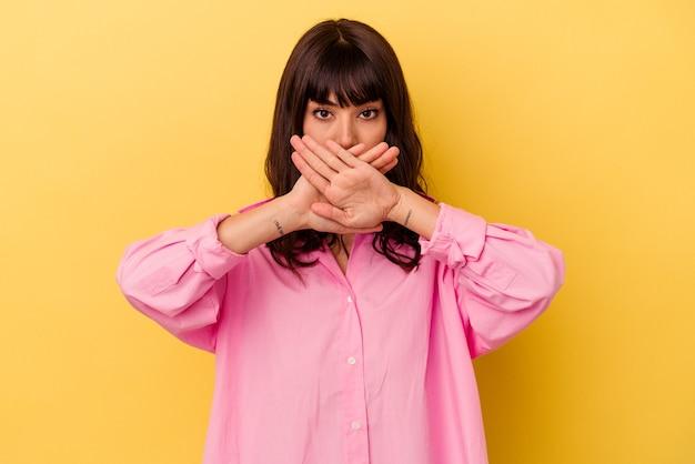 Giovane donna caucasica isolata su sfondo giallo che fa un gesto di rifiuto