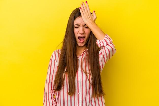 Giovane donna caucasica isolata su sfondo giallo dimenticando qualcosa, schiaffeggiando la fronte con il palmo e chiudendo gli occhi.