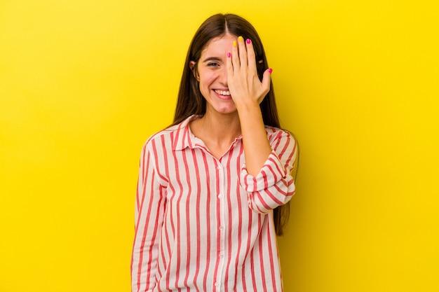 Giovane donna caucasica isolata su sfondo giallo divertendosi coprendo metà del viso con il palmo.