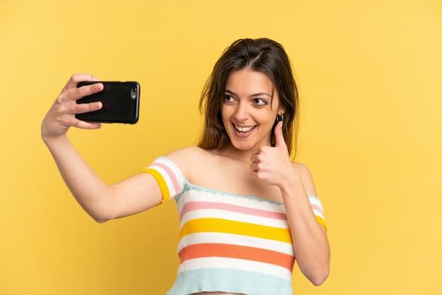 Giovane donna caucasica isolata su sfondo giallo che fa un selfie con il cellulare