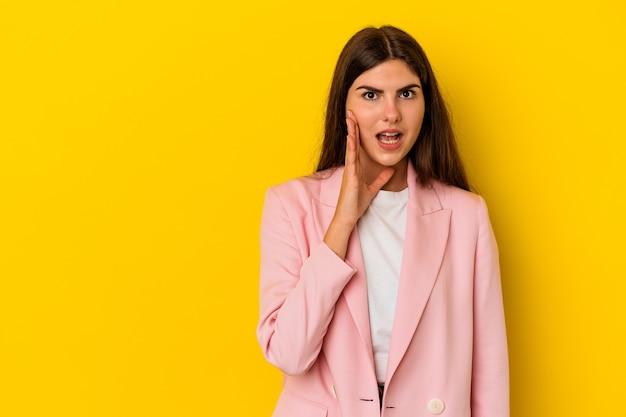 La giovane donna caucasica isolata su sfondo giallo grida forte, tiene gli occhi aperti e le mani tese.