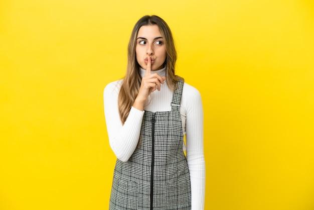 Giovane donna caucasica isolata su sfondo giallo che mostra un segno di silenzio gesto mettendo il dito in bocca
