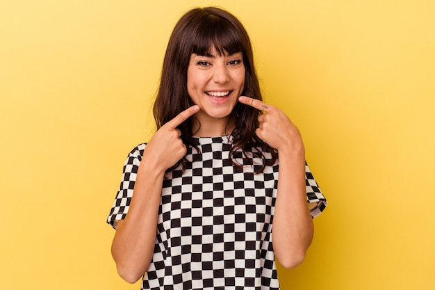 Giovane donna caucasica isolata su sfondo giallo sorrisi, puntando le dita alla bocca.