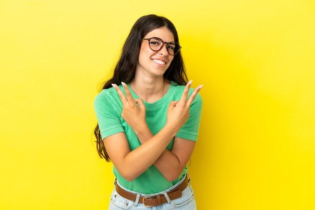 Giovane donna caucasica isolata su fondo giallo che sorride e che mostra il segno di vittoria