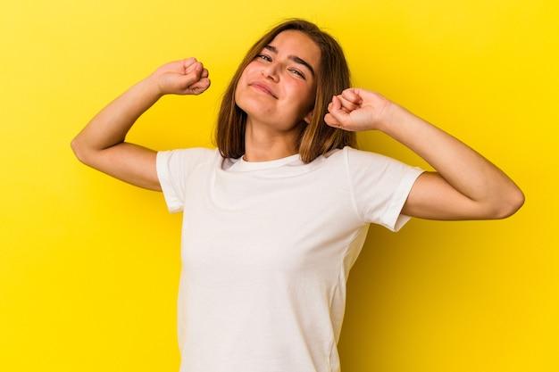 Giovane donna caucasica isolata su sfondo giallo che allunga le braccia, posizione rilassata.