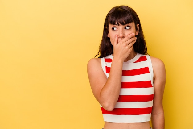Giovane donna caucasica isolata su sfondo giallo premurosa in cerca di uno spazio copia che copre la bocca con la mano.