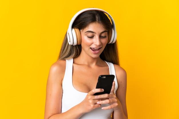 Giovane donna caucasica isolata sulla musica d'ascolto gialla e che osserva al cellulare