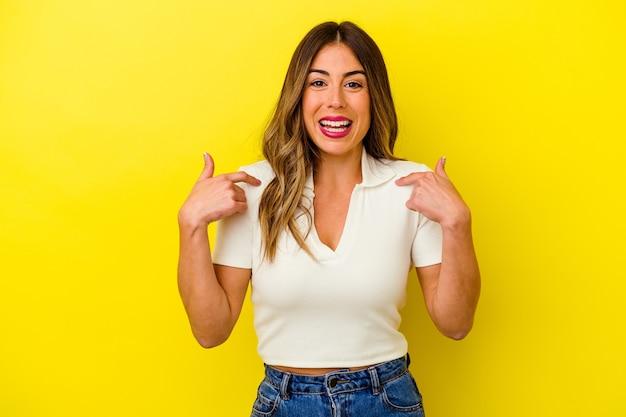 Giovane donna caucasica isolata su giallo sorpreso indicando con il dito, sorridendo ampiamente.