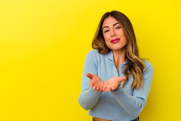 Giovane donna caucasica isolata sul muro giallo piegando le labbra e tenendo le palme per inviare un bacio d'aria.