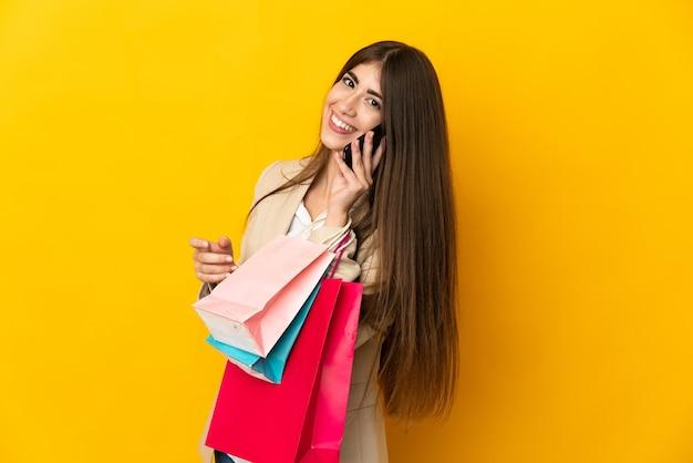 Giovane donna caucasica isolata sulla parete gialla che tiene i sacchetti della spesa e chiama un amico con il suo telefono cellulare