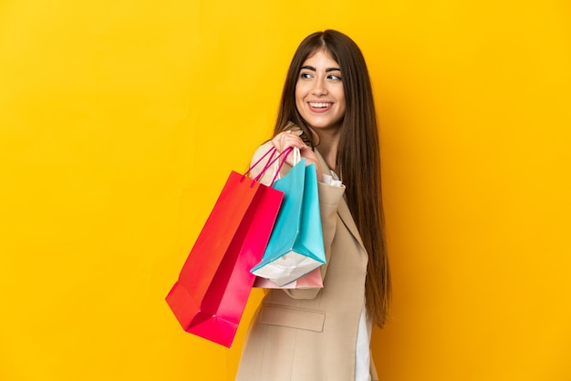 Giovane donna caucasica isolata sulla parete gialla che tiene i sacchetti della spesa e guardando indietro