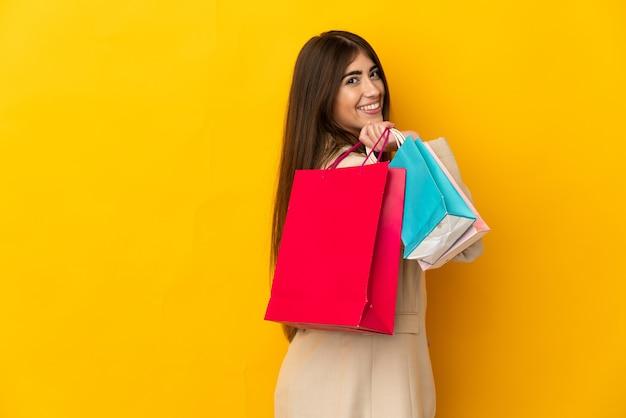 Giovane donna caucasica isolata sulla parete gialla che tiene i sacchetti della spesa e sorridente