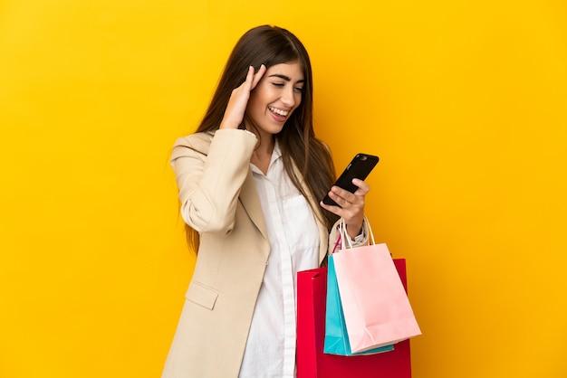 Giovane donna caucasica isolata sulla parete gialla che tiene i sacchetti della spesa e scrive un messaggio con il suo telefono cellulare ad un amico