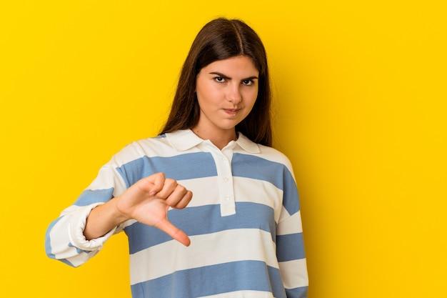 Giovane donna caucasica isolata sulla parete gialla che mostra il pollice verso il basso
