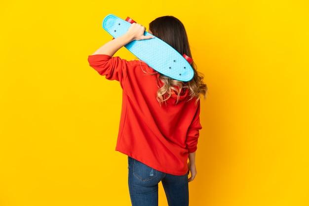 Giovane donna caucasica isolata sulla parete gialla con un pattino in posizione posteriore