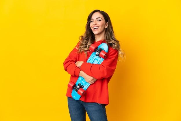 Giovane donna caucasica isolata sulla parete gialla con un pattino con l'espressione felice