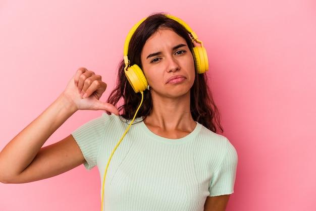 Giovane donna caucasica che ascolta musica isolata su sfondo rosa che mostra un gesto di antipatia, pollice verso. concetto di disaccordo.
