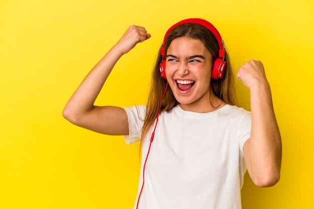 Giovane donna caucasica che ascolta musica isolata su fondo giallo che alza il pugno dopo una vittoria, concetto del vincitore.
