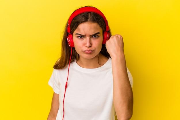 Giovane donna caucasica che ascolta la musica isolata su fondo giallo che mostra il pugno alla macchina fotografica, espressione facciale aggressiva.