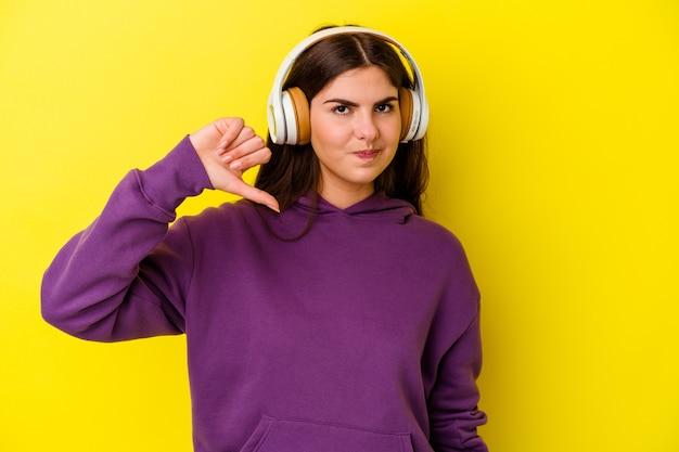 Giovane donna caucasica che ascolta la musica con le cuffie isolate su sfondo rosa che mostra un gesto di antipatia, i pollici verso il basso. concetto di disaccordo.