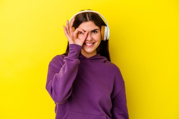 La giovane donna caucasica che ascolta la musica con le cuffie isolate sulla parete rosa ha eccitato mantenendo il gesto giusto sull'occhio.