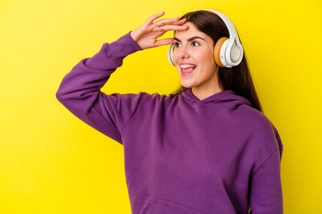 Giovane donna caucasica che ascolta la musica con le cuffie isolate sulla parete rosa che guarda lontano tenendo la mano sulla fronte.