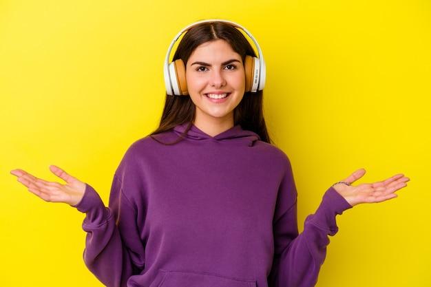 Giovane donna caucasica che ascolta la musica con le cuffie isolate sulla parete rosa che mostra un'espressione benvenuta.