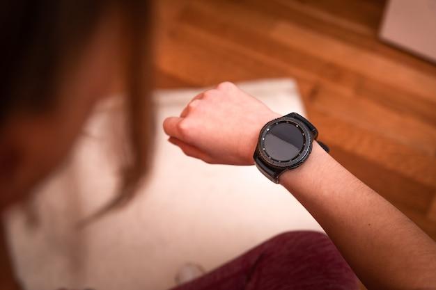 Giovane donna caucasica guardando l'orologio sportivo mentre si fa esercizi a casa