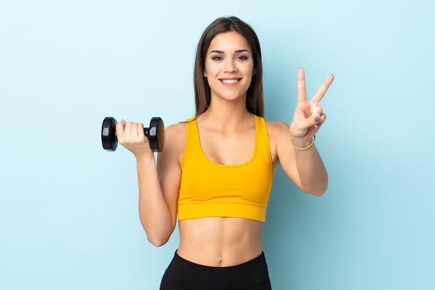 Giovane donna caucasica che fa sollevamento pesi sul blu che sorride e che mostra il segno di vittoria