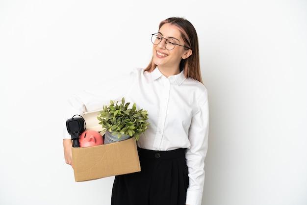 Giovane donna caucasica che si muove nella nuova casa tra scatole isolate su sfondo bianco, guardando al lato e sorridente
